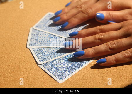 Female hands with blue fingernails spread pack of blue playing cards on wooden table. - Stock Photo