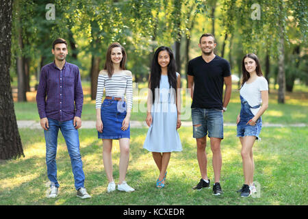 Happy smiling student friends women and men standing together outdoors. Portrait in full growth of five young confident - Stock Photo