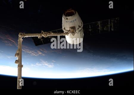 The commercial supply ship SpaceX dragon is grabbed by the CanadaArm2 robotic arm for docking to the International - Stock Photo