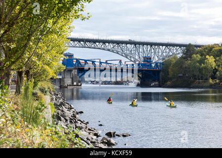 Seattle, Washington: Group of kayakers paddling along the Fremont Cut towards Lake Union under the Fremont Bridge. - Stock Photo