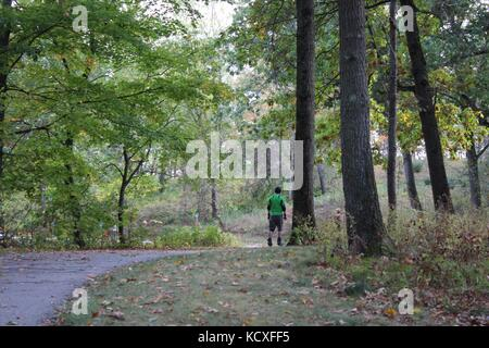 People enjoying the day in the woods on a biking and walking path with family and friends outside at a park exercising and fitness