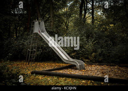 Old abandoned playground with slide in autumn - Stock Photo
