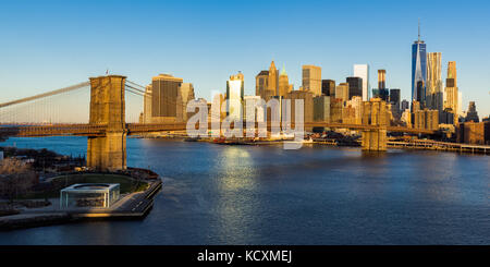 Sunrise on the Brooklyn Bridge, the East River and the skyscrapers of Lower Manhattan (panoramic). New York City - Stock Photo