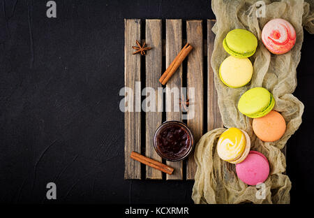 Colorful macaroons and a  jar of honey on a wooden background. Flat lay. Top view - Stock Photo