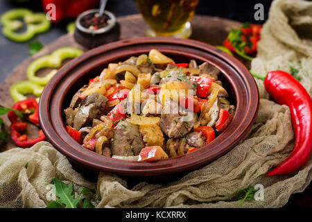 Roast chicken liver with vegetables on wooden background. - Stock Photo