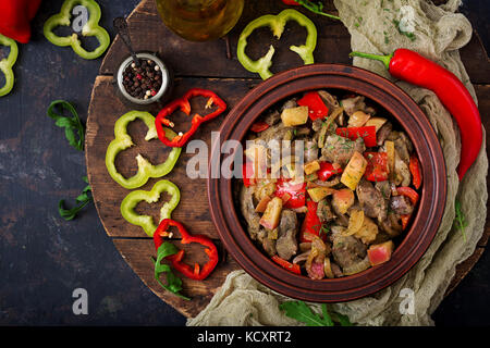 Roast chicken liver with vegetables on wooden background. Flat lay. Top view - Stock Photo
