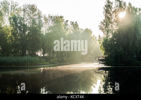 Sun rays trough birch branches. Reflections on river surface. Little  harbor. - Stock Photo
