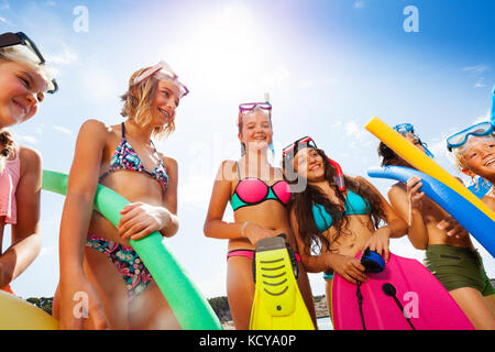 Close shot of laughing group of children in swimsuits with flippers, body boards and scuba masks - Stock Photo