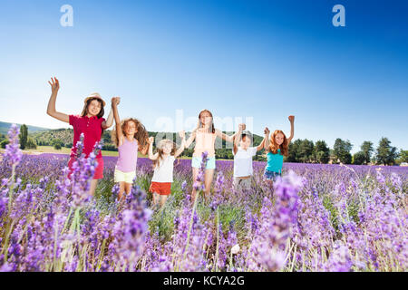 Six happy kids, age-diverse boys and girls, holding hands while standing in line in lavender field, Provence - Stock Photo