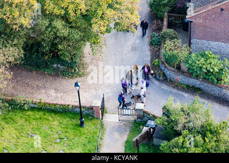 Dog walkers gather at the churchyard gate of St Mary the Virgin church  in Happisburgh, Norfolk., UK. Viewed from - Stock Photo