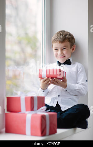 happy cute little boy wearing white shirt and bow tie near window holding gift - Stock Photo