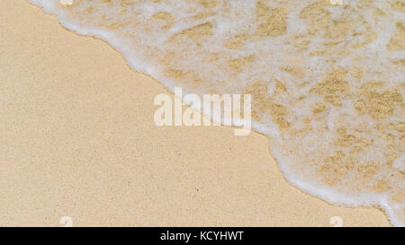 Gentle wave with foam rolling to the sandy beach - Stock Photo