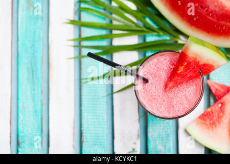 Watermelon smoothie, fresh juice on colorful wooden background with palm leaves. Top view. Copy space. - Stock Photo