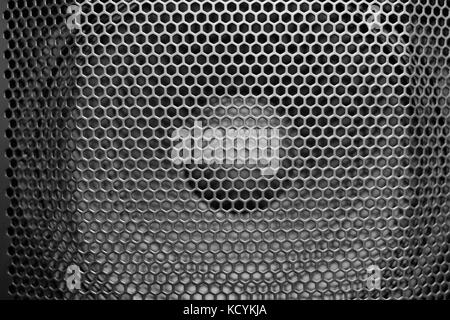 Black perforated metal speaker grill cover. Close up shot in black and white. - Stock Photo