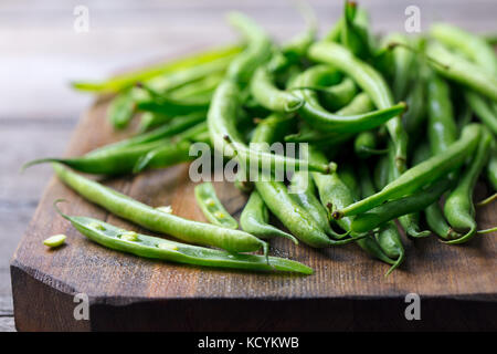 Green beans on wooden cutting board. Go green concept - Stock Photo