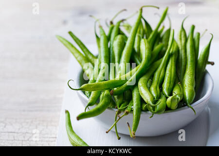 Green beans in white bowl on cutting board - Stock Photo