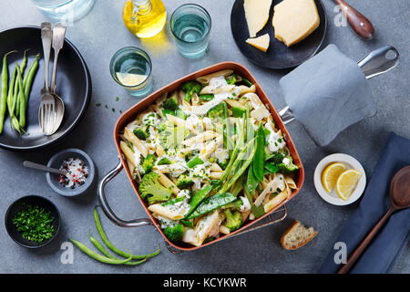 Pasta with green vegetables and creamy sauce in copper saucepan. Grey stone background. Top view. - Stock Photo