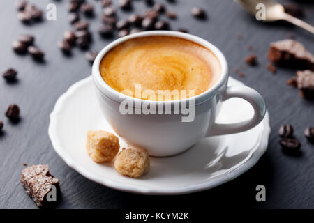 Coffee espresso in white cup on black slate background. - Stock Photo
