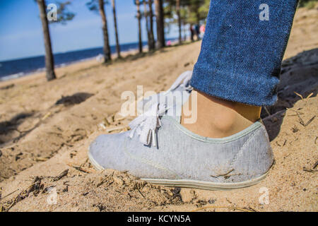 Legs in jeans and sneakers on the sand. - Stock Photo