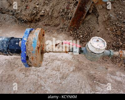 Old drink waser pipe, hydrometer and  shut-off valve  on  plastic tube. Repairing of drink water system. Open excavation - Stock Photo