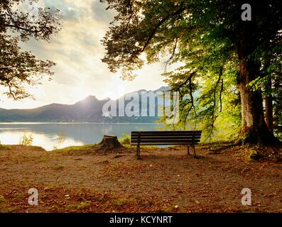 Empty wooden bench at mountain lake. Bank under beeches tree, mountains at horizon and in water mirror. Vintage - Stock Photo