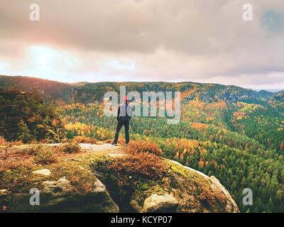 Alone tourist with outdoor sportswear and backpack stand on cliff edge  and watching into colorful autumn valley - Stock Photo