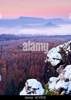 First powder snow cover on sandstone rocks above valley park. Heavy mist in valley bellow view point. Chilly autumnal - Stock Photo