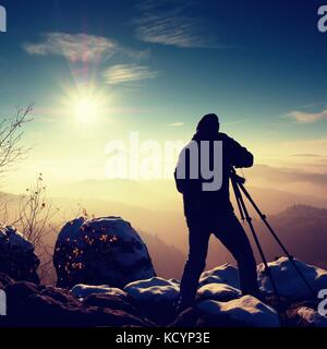 Professional photographer takes picture of freeze autumnal daybreak, rocks covered with fresh powder snow. Stony - Stock Photo
