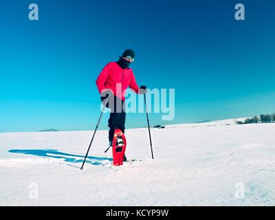Man cleaning snowshoe. Winter tourist with snowshoes walk in snowy drift. Sunny freeze weather. Hiker in pink sports - Stock Photo