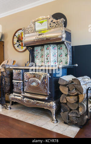 Antique black cast iron and chrome Royal wood burning cook stove in the family room inside an old reconstructed - Stock Photo