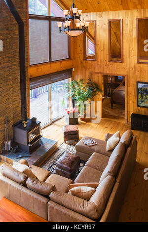 Toip view of tan leather sectional sofa and wood burning stove in living room area of the great room with cathedral - Stock Photo