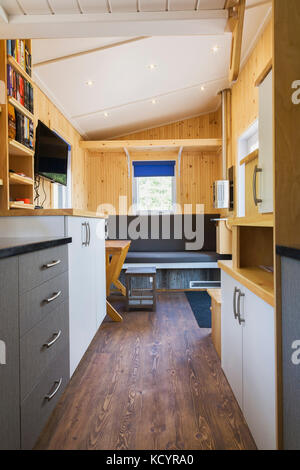 Brown stained pinewood floor and view of kitchen counters, grey and white melamine cabinets and main sitting area - Stock Photo