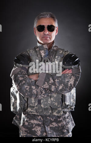 Portrait Of A Mature Soldier Wearing Sunglasses Over Black Background - Stock Photo