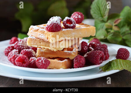 Waffles with raspberry on a old wooden table . - Stock Photo