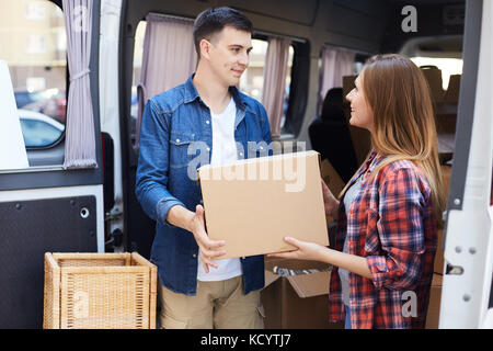 Portrait of smiling young man and woman unloading boxes from moving van outdoors - Stock Photo