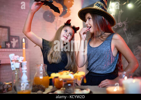 Portrait of two teenage girls wearing Halloween costumes playing with toy bat in decorated room during party - Stock Photo