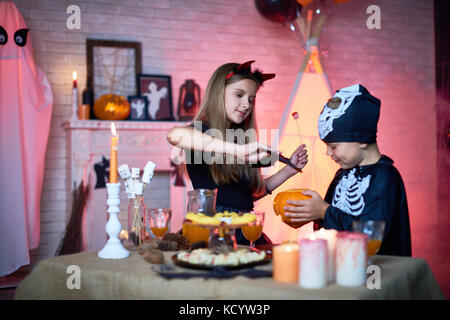 Portrait of children in Halloween costumes playing with carved pumpkin in decorated room during party - Stock Photo
