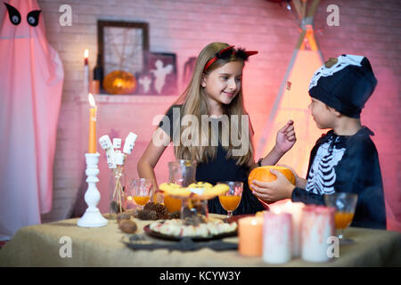 Portrait of two children, boy and girl wearing Halloween costumes chatting during party standing at table with sweets - Stock Photo