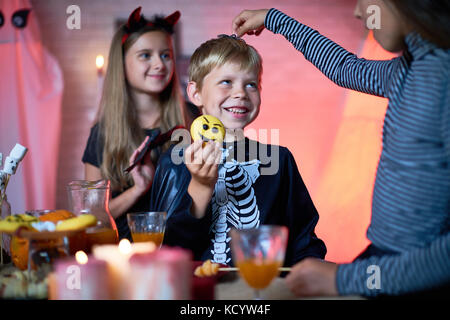 Portrait of children wearing Halloween costumes playing in decorated room during party, girl putting toy spider - Stock Photo