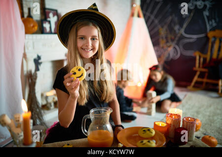 Portrait of pretty little girl dressed in Halloween costume posing with vampire cookie in decorated room, other - Stock Photo