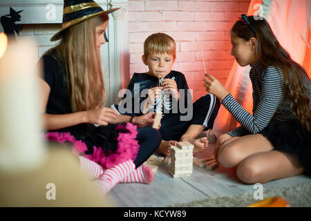 Portrait of three children wearing Halloween costumes, one boy and two girls, playing tower game in decorated studio - Stock Photo