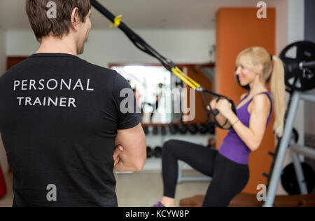 Personal trainer, with his back facing the camera, looking at his client - Stock Photo