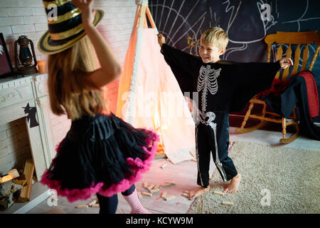 Portrait of two kids wearing Halloween costumes having fun playing in decorated studio - Stock Photo