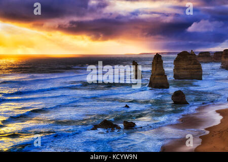 Colourful warm sunset over southern ocean horizon warming standing strong limestone rock formations- twelve apostles - Stock Photo