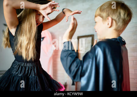 Portrait of teenage girl wearing witch costume trying to scare little boy on Halloween - Stock Photo