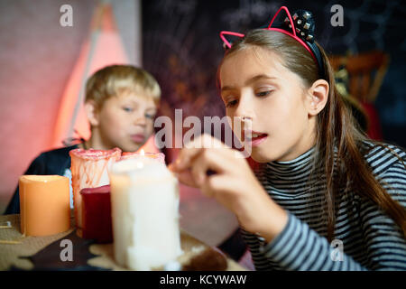 Portrait of pretty little girl lighting up candles on Halloween in decorated room, little boy wearing costume in - Stock Photo