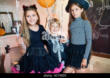 Portrait of three happy children wearing costumes posing with balloons in decorated room celebrating Halloween - Stock Photo