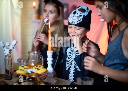Portrait of handsome little boy wearing skeleton costume enjoying tasty fried marshmallows while celebrating Halloween - Stock Photo