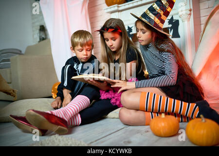 Group of cute kids wearing Halloween costumes gathered together at living room decorated for holiday and reading - Stock Photo