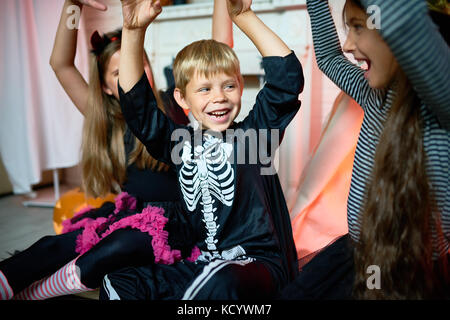Portrait of smiling little boy wearing skeleton costume having fun while celebrating Halloween with friends at home - Stock Photo